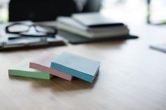 稠粘的笔记,镜片,在办公桌上的笔记本 事务,工作 图库摄影