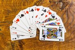 稳定,在老橡木桌上的啤牌卡片 库存照片