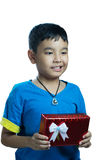 滑稽亚洲孩子的看起来,当接受一个礼物 图库摄影