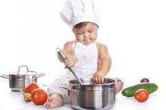 滑稽可爱男婴厨师开会和使用 免版税库存照片