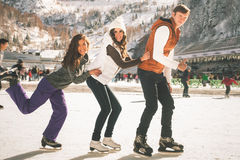 滑稽少年女孩和男孩滑冰室外,滑冰场 库存照片