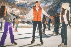 滑稽少年女孩和男孩滑冰室外,滑冰场 免版税库存图片