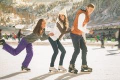 滑稽少年女孩和男孩滑冰室外,滑冰场 免版税库存照片