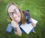 滑稽广角讨厌青少年与书和铅笔 免版税库存照片
