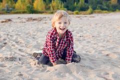 滑稽微笑的笑的白白种人儿童孩子白肤金发的男孩坐的使用与在海滩的沙子在日落 免版税库存照片