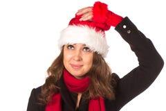滑稽掠夺有红色蓬松圣诞老人帽子的圣诞节女孩 免版税图库摄影