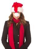 滑稽掠夺有红色蓬松圣诞老人帽子的圣诞节女孩 图库摄影