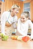滑稽烹调与母亲和她的十几岁的女儿Kitche的 免版税图库摄影