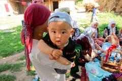 滑稽的亚裔男孩坐他的母亲的胳膊在一个家庭假日期间 库存图片