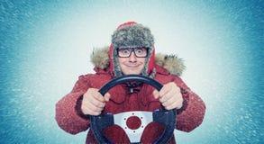 滑稽的人在冬天穿衣与方向盘,雪飞雪 概念汽车司机 库存照片