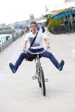 滑稽的人有乐趣骑马自行车在镇里 库存照片