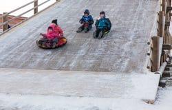滑稽的人民滑下来冰幻灯片 免版税库存照片