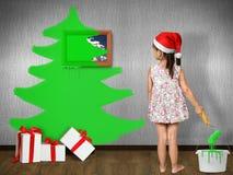 滑稽的儿童女孩穿戴的圣诞老人帽子,画在墙壁上的圣诞树 免版税库存照片