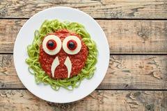 滑稽的创造性的万圣夜食物妖怪绿色意粉面团用假血液西红柿酱 免版税库存照片