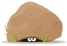 在大石头之下的动画片动物眼睛 免版税库存图片