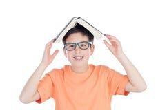 滑稽的十几岁的男孩十三与在头的一本书 免版税图库摄影