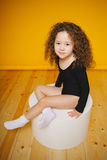 滑稽的卷曲小女孩微笑在橙色背景的演播室 拷贝空间 免版税库存图片