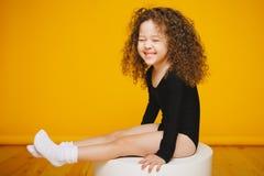 滑稽的卷曲小女孩笑在橙色背景的演播室 拷贝空间 库存图片