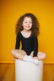 滑稽的卷曲小女孩笑在橙色背景的演播室 免版税图库摄影