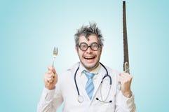 滑稽的古怪和疯狂的外科医生医生拿着异常的仪器 免版税库存图片