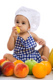 滑稽的可爱的婴孩用绿色苹果和不同的果子 免版税库存图片
