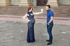 滑稽的图象 Ð期待婴孩的¡ ouple :妇女拿着一个标志 免版税库存照片