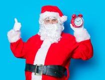 滑稽的圣诞老人获得与闹钟的一个乐趣 库存图片