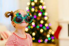 戴滑稽的圣诞节眼镜的小女孩 免版税库存图片