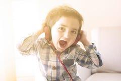 滑稽的在耳机的婴孩听的音乐 免版税库存照片