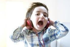 滑稽的在耳机的婴孩听的音乐 库存图片