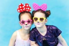 滑稽的太阳镜的两个微笑的魅力女孩在蓝色背景 免版税库存图片