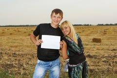 滑稽的夫妇显示空白的纸 免版税库存图片