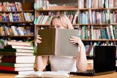 滑稽的女学生在图书馆里 免版税库存照片