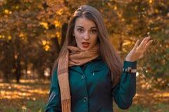 滑稽的女孩在公园站立在张您的嘴旁边并且涂她的手 库存图片
