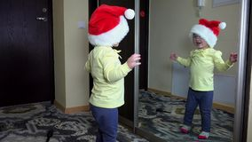 滑稽的女孩在头和跃迁的被投入的圣诞老人帽子在镜子前面 粗心大意的童年 影视素材