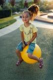 滑稽的女孩在黄色球跳 免版税图库摄影