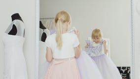 滑稽的女孩尝试在一件新的礼服的6年 看他的在镜子的反射 股票视频