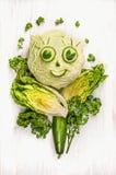 滑稽的女孩面孔由绿色菜、黄瓜和莴苣制成在白色木 免版税图库摄影