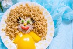 滑稽的女孩食物面孔用炸肉排,面团面条和菜 图库摄影