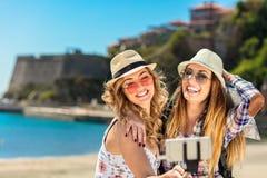 滑稽的女性朋友在度假采取在海滩的selfies与一个巧妙的电话 免版税库存图片