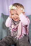 滑稽的女婴用在她的头的手 库存图片