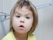 滑稽的女婴画象谈话与逗人喜爱的甜面颊 免版税库存照片