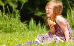 滑稽的嬉戏的小女孩有野餐在公园 库存照片