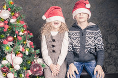 滑稽的孩子在近圣诞节假日装饰了圣诞树 免版税库存图片