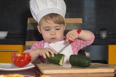 滑稽的孩子坐厨房用桌 与刀子的儿童黄瓜切开 图库摄影