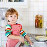 滑稽的孩子男孩在家帮助的和洗涤的盘 库存图片