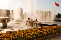 滑稽的家庭在一热的天的喷泉附近跳 库存图片