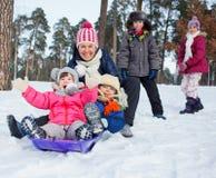 滑稽的家庭在冬天风景sledging 库存照片