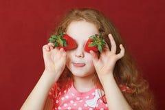 滑稽的小女孩吃着草莓 免版税图库摄影