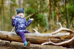 滑稽的小女孩坐日志在森林远足期间 免版税库存照片